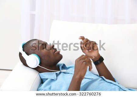 Handsome African American man with headphones lying on sofa close up