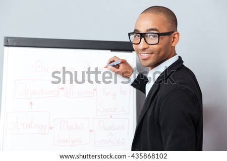 Handsome african american young man making presentation of business plan on flipchart - stock photo