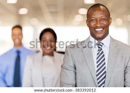 handsome african businessman standing in front of colleagues