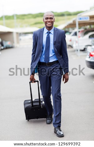 handsome african businessman walking in airport parking lot - stock photo