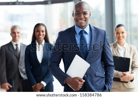 handsome african businessman with group of businesspeople on background - stock photo