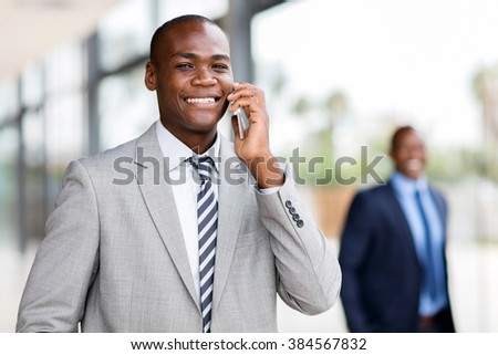 handsome african corporate worker talking on mobile phone - stock photo