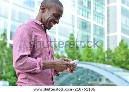 Handsome african man messaging his friend - stock photo