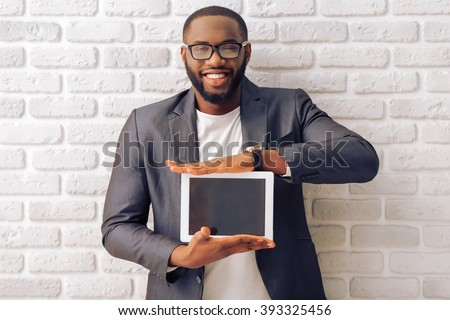 Handsome Afro American businessman in gray classic jacket and glasses is showing a tablet and smiling, standing against brick wall - stock photo