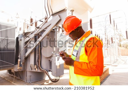 handsome afro american electrical engineer writing on clipboard in power plant
