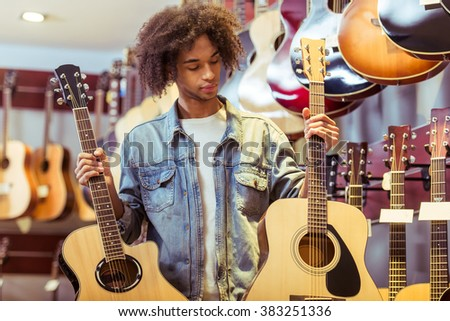 Handsome Afro-American man holding two guitars in both hands and examining them while standing in a musical shop