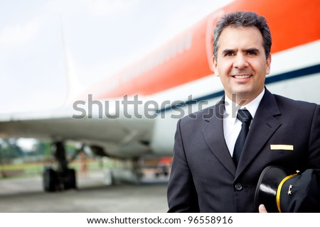 Handsome airplane pilot at the airport smiling - stock photo