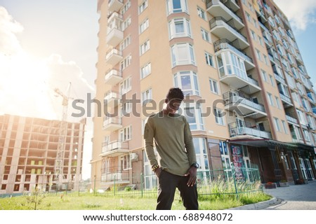 Handsome and attractive african american man posing next to the tall building on a street.