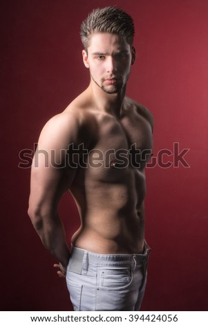 Handsome and attractive shirtless male model against a red background - Hazy yellowish erotic look to it - stock photo