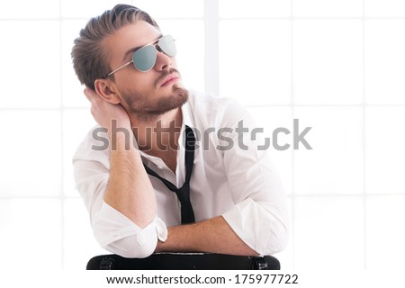 Handsome and confident man. Thoughtful young man in sunglasses holding head in hand and looking away while sitting on the chair - stock photo