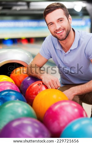 Handsome and confident player. Cheerful young man sitting near bowling balls and smiling against bowling alleys  - stock photo