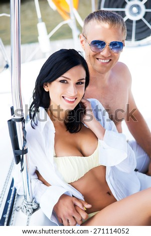 Handsome and rich man and a beautiful and sexy woman in swimsuit relaxing on a sailing boat - stock photo