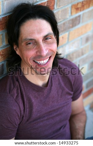handsome and rugged man sitting outside smiling - stock photoHandsome Rugged Man