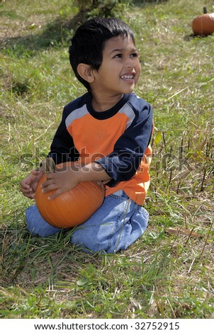 Handsome and smiling kid sitting with a pumpkin - stock photo