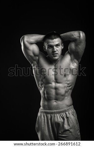Handsome and strong bodybuilder shows his muscles isolated on dark background