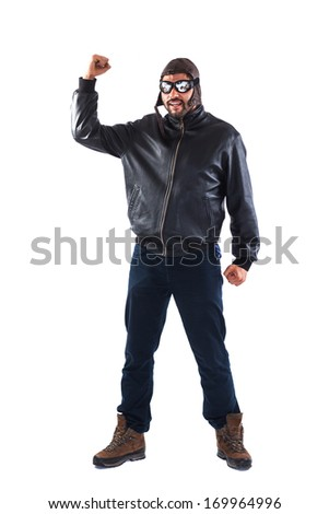 Handsome and strong young man dressed as a pilot is holding his fist upwards - isolated on white - stock photo