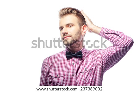 Handsome and stylish. Handsome bearded young man in bow tie touching his hair and looking at camera while standing against white background - stock photo