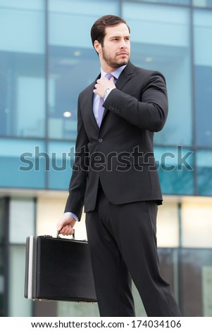 handsome and successful businessman in front of an office building with a briefcase - stock photo