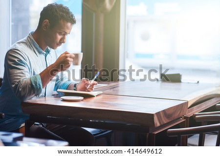 Handsome Arabian man is spending time in cafeteria - stock photo