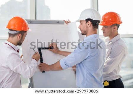 Handsome architect and his colleagues are drawing sketches of building. They are taking measurements with a ruler and compass. The men are looking at the board of plan with concentration