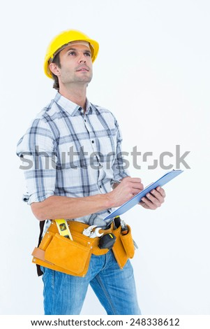 Handsome architect writing notes on clip board over white background
