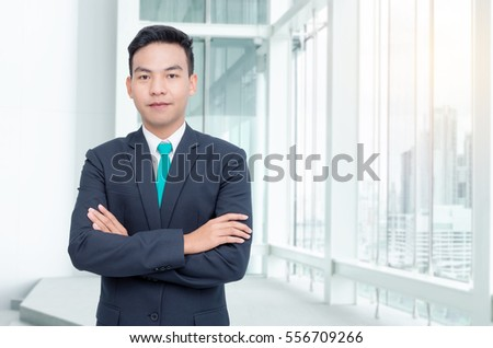 Handsome asian businessman standing in office