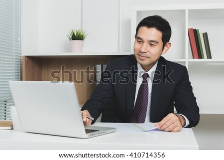 Handsome Asian businessman using laptop computer in the office - soft tone, selective focus - stock photo