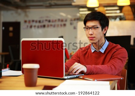 Handsome asian man in glasses working on laptop in office - stock photo