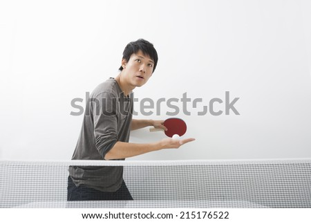 Handsome Asian man playing ping pong - stock photo