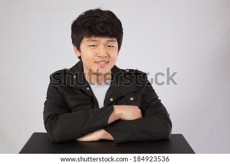 Handsome Asian teenager sitting at a table with his hands folded and looking at the camera with a thoughtful expression