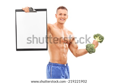 Handsome athlete holding a clipboard and a broccoli dumbbell isolated on white background - stock photo