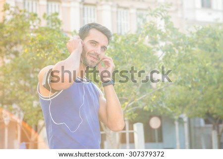 Handsome athlete smiling and putting in headphones in the city - stock photo