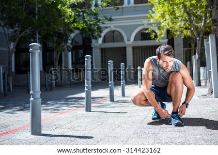 Handsome athlete tying his shoe laces on a sunny day - stock photo