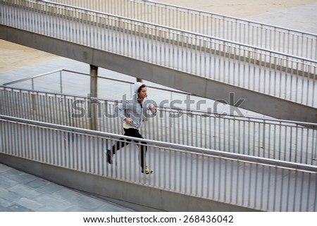 Handsome athletic man in sweatshirt running up little bridge while training at early morning outdoors - stock photo