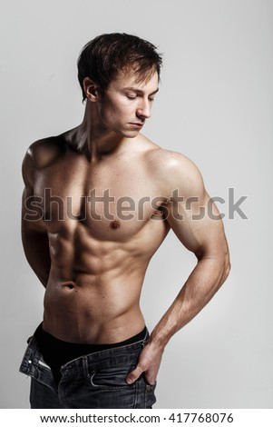 Handsome athletic man looking at side in unbuttoned jeans. Strong bodybuilder with six pack,perfect abs, shoulders, biceps, triceps and chest. Great fitness body. Ideal for commercial. Gray background
