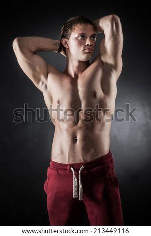 Handsome athletic man posing on dark background - stock photo