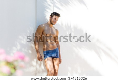 Handsome athletic man posing outdoor in beach shorts - stock photo