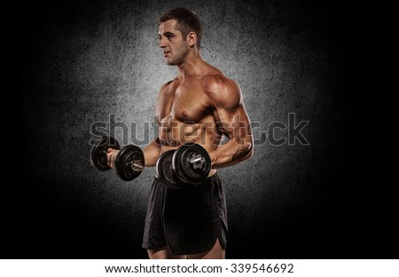 Handsome athletic man power training with dumbbells pumping muscle.