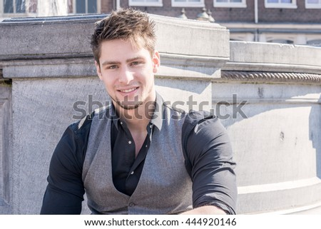Handsome attractive trendy young man outdoors. Attractive male model outside in bright light sunny weather. - stock photo