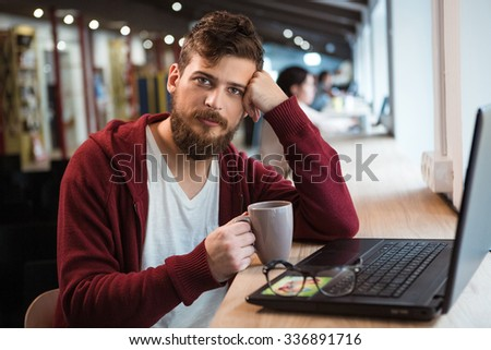 Handsome attractive young guy drinking coffe and using laptop siting in the office - stock photo