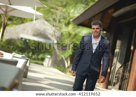Handsome, attractive young man walking outside restaurant across terrace. Beautiful tropical destination restaurant, lounge bar with terrace.