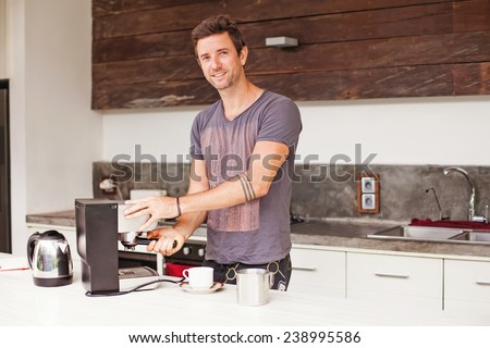 handsome australian man making coffee with a coffee machine - stock photo