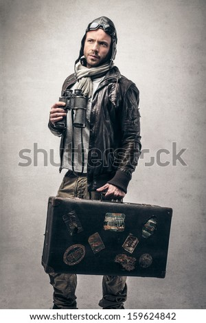 handsome aviator with binoculars in hand and vintage suitcase - stock photo