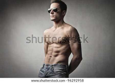 Handsome bare-chested man wearing fashion sunglasses - stock photo