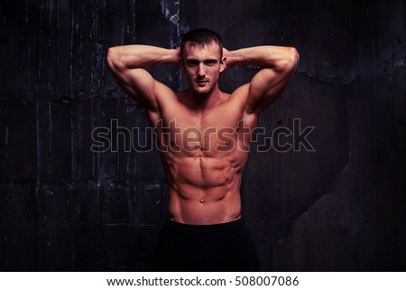 Handsome bare-chested man with perfect abs and well-trained body