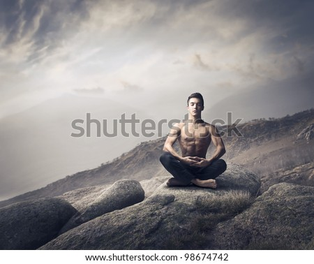 Handsome bare-chested young man doing yoga on a rock - stock photo