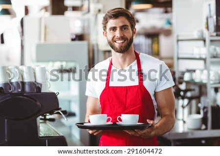 Handsome barista holding two cups of coffee in the cafe - stock photo