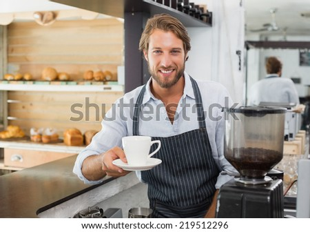 Handsome barista offering a cup of coffee to camera at the coffee shop - stock photo