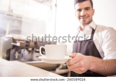 Handsome barista offering a cup of coffee to you at the coffee shop. Blurred background. - stock photo