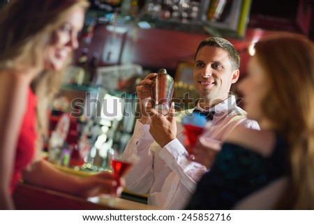 Handsome barman chatting to customers in a bar - stock photo
